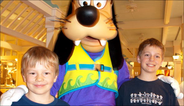Sam and Max embrace the extremely tall Goofy